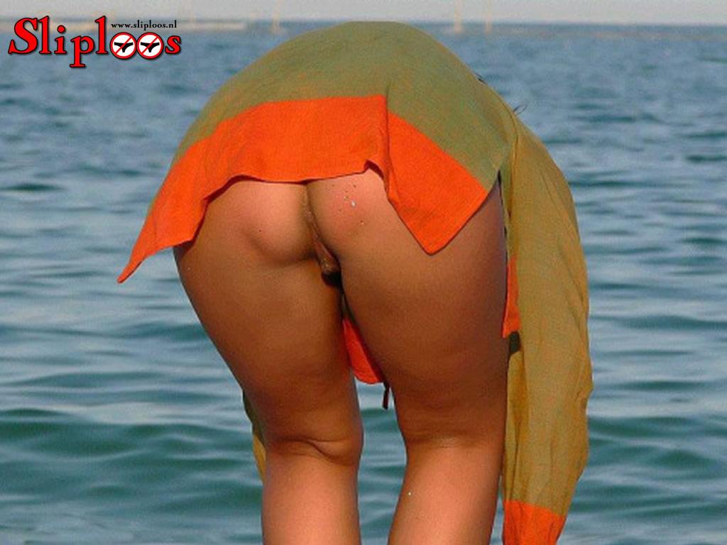 Zonder slipje aan bukken op het strand!