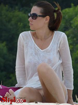 Vrouwtje zit zonder slipje aan op het strand!